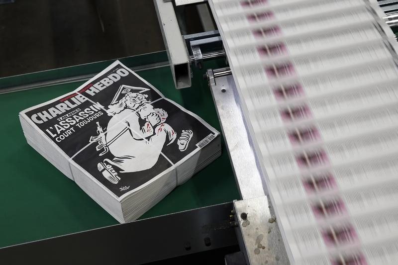 "Packed copies of the latest edition of French weekly newspaper Charlie Hebdo with the title ""One year on, The assassin still on the run"" are seen at a printing house near Paris, France, January 4, 2016. France this week commemorates the victims of last year's Islamist militant attacks on satirical weekly Charlie Hebdo and a Jewish supermarket with eulogies, memorial plaques and another cartoon lampooning religion. REUTERS/Benoit Tessier - RTX2100T"